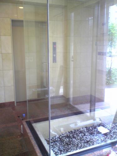 ガラスフィルム施工前の現場写真。マンションエントランス。玄関から写真奥エレベータまでの通路に小石が敷いた明かりとりがありその三面をガラスが入ってるという場所です。